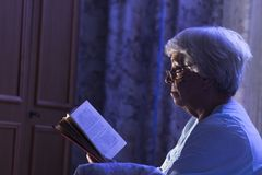 A senior woman reading her book before sleeping Royalty Free Stock Photos