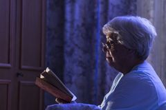 A senior woman reading her book before sleeping Stock Image