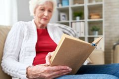 Senior Woman Reading at Home. Low angle portrait of white-haired woman reading book while enjoying leisure time at home, focus on book in wrinkled hands, copy Stock Images