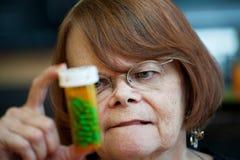 Senior woman reading instructions on prescription. Bottle Royalty Free Stock Images
