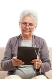 Senior woman reading and listening music Stock Image
