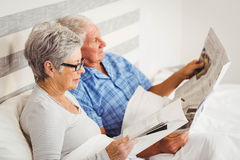 Senior woman reading magazine and senior man reading newspaper Royalty Free Stock Photography