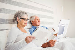 Senior woman reading magazine and senior man reading newspaper Royalty Free Stock Photos