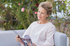 Senior woman reading magazine. Senior woman reading a magazine sitting on a couch outdoor. Happy elderly woman reading a gossip magazine in her free time. Mature Royalty Free Stock Photo