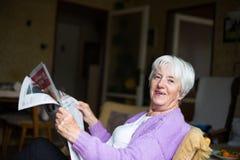 Senior woman reading morning newspaper Stock Images