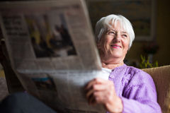 Senior woman reading morning newspaper. Sitting in her favorite chair in her living room, looking happy Stock Image