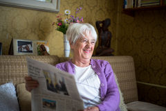 Senior woman reading morning newspaper Stock Images