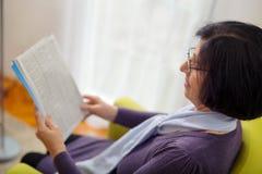 Senior woman reading news paper on sofa at home Royalty Free Stock Photos