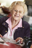 Senior woman reading newspaper. At table Royalty Free Stock Images