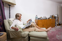 Senior woman reading newspaper while relaxing on armchair at home Stock Photo