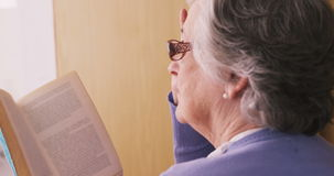 Senior woman reading a novel. At home stock video footage