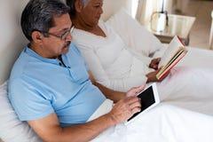 Senior woman reading a novel and senior man using digital tablet on bed Royalty Free Stock Image