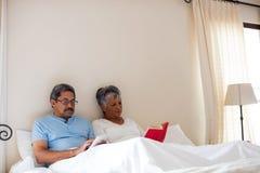 Senior woman reading a novel and senior man using digital tablet on bed Royalty Free Stock Photo