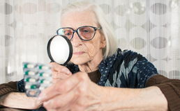 Senior woman reading pill name with magnifying glass Stock Photo