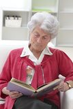 Senior woman reading. Smiling Grey haired senior woman relaxing at home reading a book Stock Images