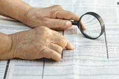 Senior woman reading stock listings. Senior woman reading stock exchange listings Stock Photography