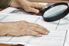 Senior woman reading stock listings. With magnifier loupe Stock Image