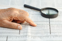 Senior woman reading stock listings. On newspaper Royalty Free Stock Photos