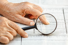 Senior woman reading stock listings. On newspaper Stock Image