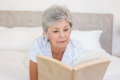 Senior woman reading story book in bed. Senior woman reading story book while lying in bed Royalty Free Stock Photos