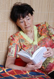 Senior woman reading thriller book Royalty Free Stock Photo
