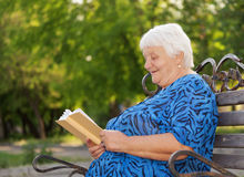 Portrait senior woman. Senior woman reads the book sitting on a bench royalty free stock photography