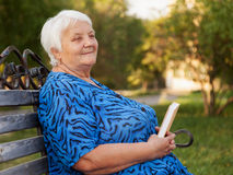 Portrait senior woman. Senior woman reads the book sitting on a bench Stock Images