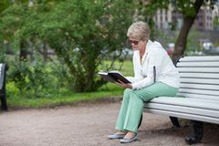 Senior woman reads book sitting on edge of long white wooden bench in summer park, copy space Stock Photos
