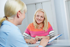 Senior woman receiving form from doctors assistant Stock Images