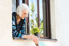 Senior woman receiving retirement check at home. Senior woman receiving retirement check on the window at home Royalty Free Stock Photos