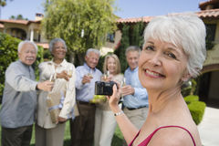 Senior Woman Recording Happy Moments. Portrait of senior women recording happy moments of multiethnic friends standing together in the background at lawn Stock Photo