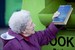 A senior woman recycling a book royalty free stock image