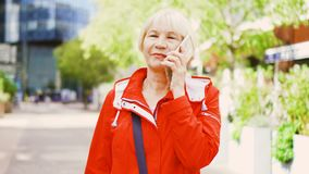 Senior woman standing outdoors using smartphone. Downtown business dictrict on background. Senior woman in red coat standing outdoors using cellhone. Retired stock video footage