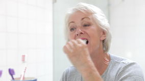 Senior Woman Reflected In Bathroom Mirror Brushing Teeth stock video