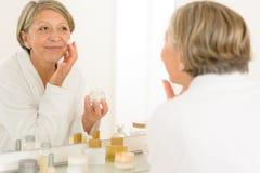 Senior woman reflection in bathroom mirror. Senior woman looking in bathroom mirror applying anti-wrinkles face cream stock photos