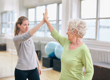 Senior woman rejoicing health success with her trainer at rehab. Senior women giving high five to her personal trainer at gym. Excited old women rejoicing health Royalty Free Stock Photography