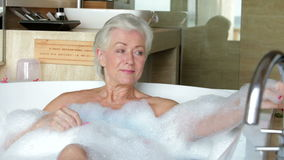 Senior Woman Relaxing In Bath Drinking Champagne stock footage
