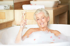 Senior Woman Relaxing In Bath Drinking Champagne Royalty Free Stock Photography