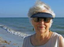 Senior woman relaxing on beach. Happy senior woman with sun visor relaxing on beach with sea in background Royalty Free Stock Photo
