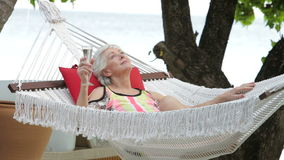 Senior Woman Relaxing In Beach Hammock With Champagne stock video footage