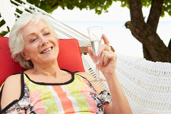 Senior Woman Relaxing In Beach Hammock With Champagne Stock Photo