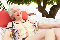 Senior Woman Relaxing In Beach Hammock With Champagne Royalty Free Stock Photos