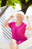 Senior Woman Relaxing In Beach Hammock. Smiling To Camera Royalty Free Stock Images