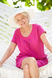 Senior Woman Relaxing In Beach Hammock. Smiling To Camera Stock Photography