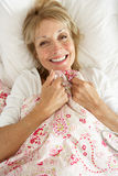 Senior Woman Relaxing In Bed Stock Photo