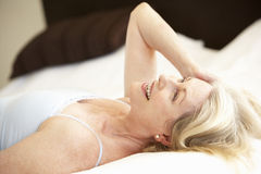 Senior Woman Relaxing On Bed Royalty Free Stock Photography