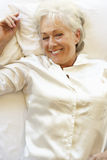 Senior Woman Relaxing In Bed Royalty Free Stock Photos