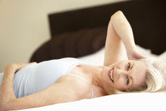 Senior Woman Relaxing On Bed Royalty Free Stock Photos