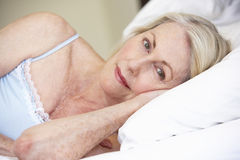 Senior Woman Relaxing On Bed Stock Photo