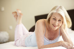 Senior Woman Relaxing On Bed Stock Photography